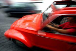 bigstock-Man-driving-fast-52416469